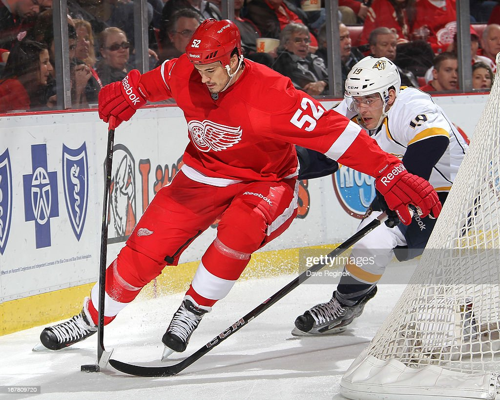 Jonathan Ericsson of the Detroit Red Wings protects the puck from Bobby Butler of the Nashville Predators during a NHL game at Joe Louis Arena on...