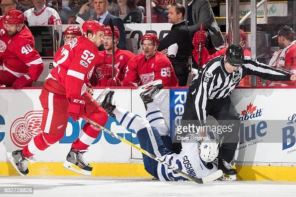 Jonathan Ericsson of the Detroit Red Wings skates behind Nikita Soshnikov of the Toronto Maple Leafs as he crashes into linesman Scott Driscoll...