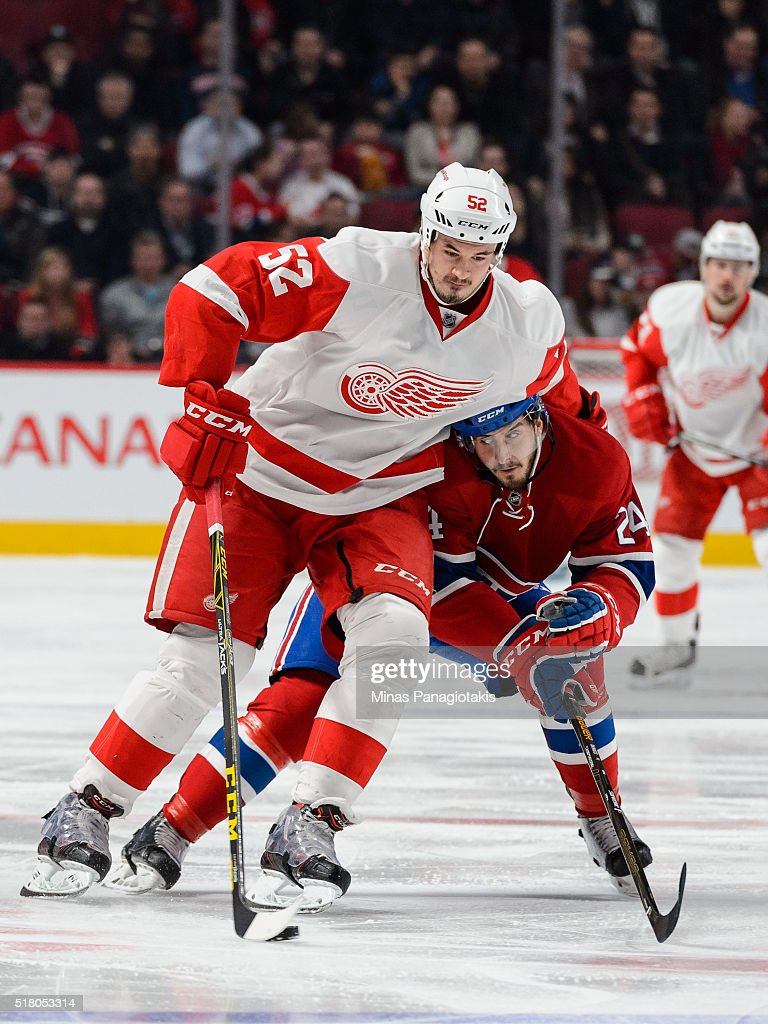 Jonathan Ericsson #52 of the Detroit Red Wings skates the puck against Phillip Danault #24 of the Montreal Canadiens during the NHL game at the Bell Centre on March 29, 2016 in Montreal, Quebec, Canada.