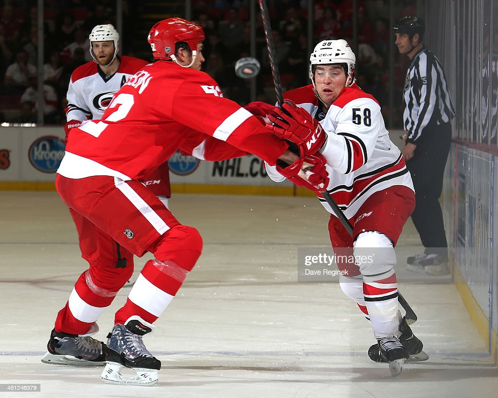 <a gi-track='captionPersonalityLinkClicked' href=/galleries/search?phrase=Jonathan+Ericsson&family=editorial&specificpeople=2538498 ng-click='$event.stopPropagation()'>Jonathan Ericsson</a> #52 of the Detroit Red Wings takes the body on Chris Terry #58 of the Carolina Hurricanes as he dumps the puck during an NHL game at Joe Louis Arena on November 21, 2013 in Detroit, Michigan.