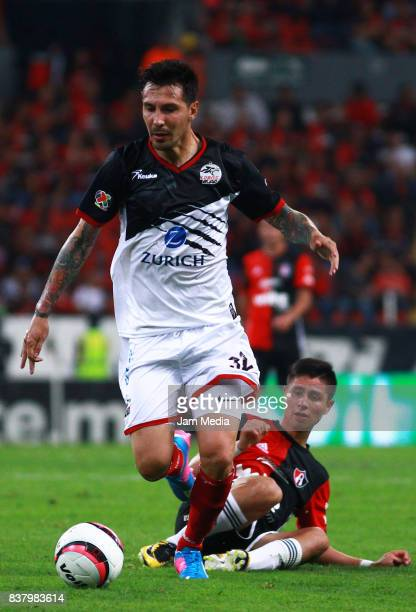Jonathan Fabbro of Lobos BUAP and Bryan Garnica of Atlas fight for the ball during the 6th round match between Atlas and Lobos BUAP as part of the...