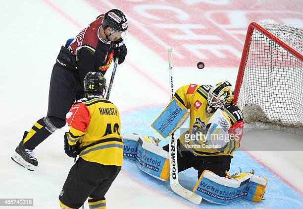 Jonathan Ferland of EV Vienna Capitals Steve Hanusch and Thomas Duba of Krefeld Pinguine during the Champions Hockey League group stage game between...