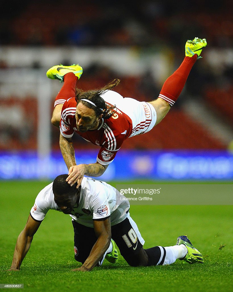 Jonathan Greening of Nottingham Forest battles with Marvin Sordell of Charlton Athletic during the Sky bet Championship match between Nottingham Forest and Charlton Athletic at City Ground on March 25, 2014 in Nottingham, England.