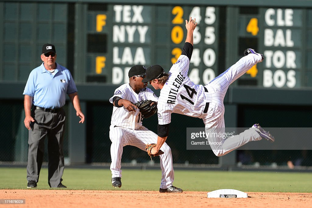 Jonathan Herrera collides with Josh Rutledge of the Colorado Rockies while trying to catch a ball off the bat of Daniel Murphy of the New York Mets...