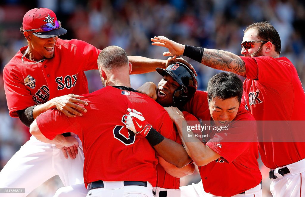 Jonathan Herrera of the Boston Red Sox celebrates with teammates after he singled in the winning run in the ninth inning during the first game of a...