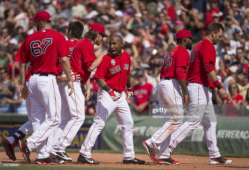 Jonathan Herrera of the Boston Red Sox is surrounded by teammates after hitting a walkoff single against the Baltimore Orioles in the ninth inning...