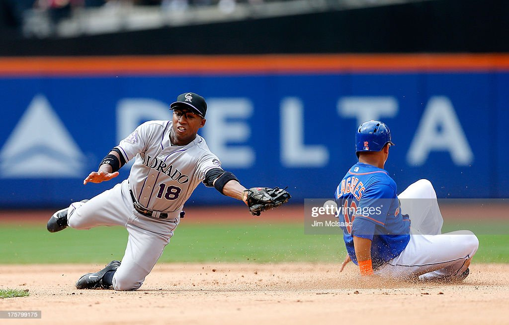 Jonathan Herrera of the Colorado Rockies can't come up with the throw as Juan Lagares of the New York Mets steals second base in the seventh inning...