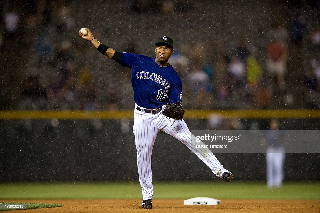 Jonathan Herrera of the Colorado Rockies makes a throw to put out a baserunner at first base as heavy rain falls in the seventh inning of a game...