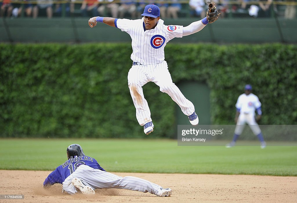Jonathan Herrera of the Colorado Rockies slides into second base as shortstop Starlin Castro of the Chicago Cubs leaps for a wild throw from catcher...