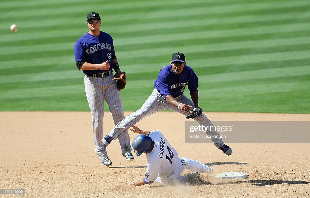 Jonathan Herrera of the Colorado Rockies throws to first base after getting the force out on Jamey Carroll of the Los Angeles Dodgers at second base...