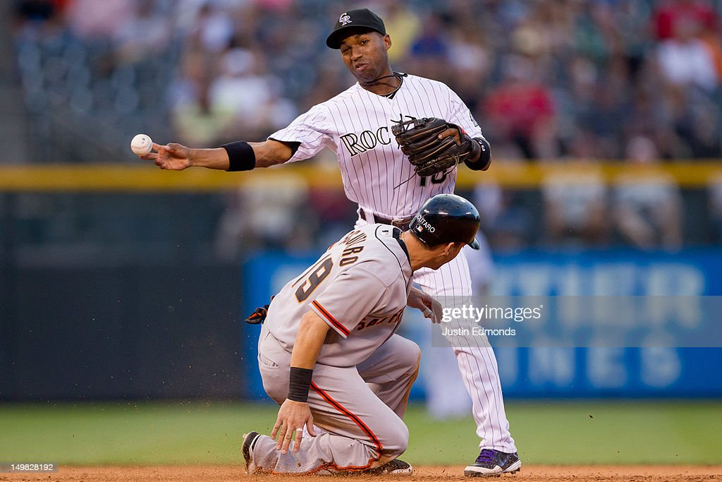 Jonathan Herrera of the Colorado Rockies throws to first base after recording the lead out at second base as Marco Scutaro of the San Francisco...