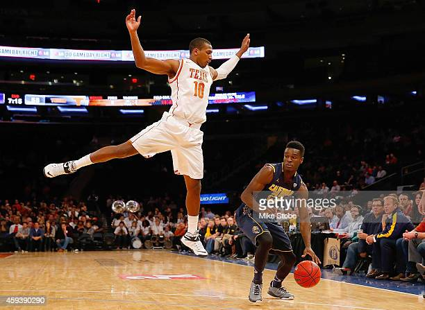 Jonathan Holmes of the Texas Longhorns defends against Jabari Bird of the California Golden Bears at Madison Square Garden on November 21 2014 in New...