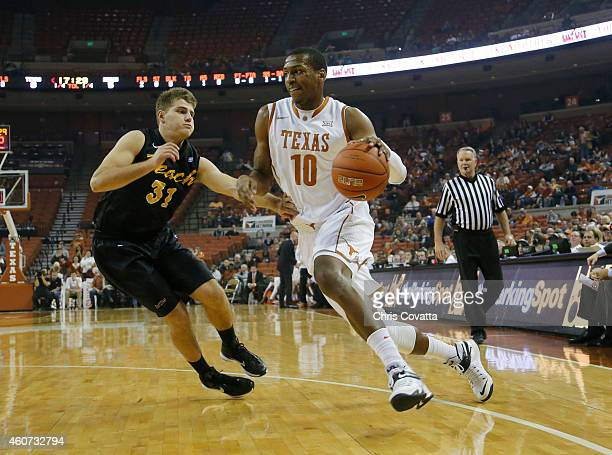 Jonathan Holmes of the Texas Longhorns drives around McKay LaSalle of the Long Beach State 49ers at the Frank Erwin Center on December 20 2014 in...