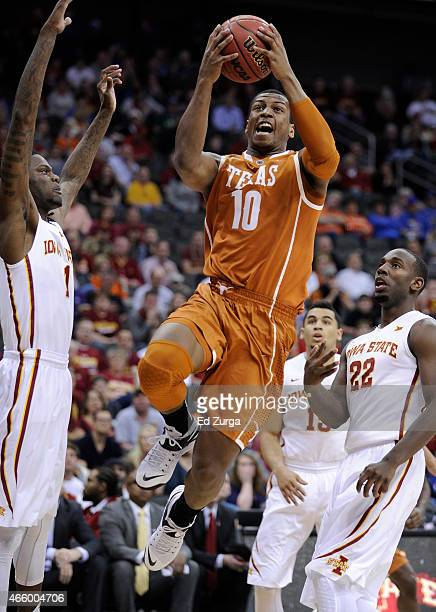 Jonathan Holmes of the Texas Longhorns goes up for a shot against Jameel McKay and Dustin Hogue of the Iowa State Cyclones during the quarterfinal...