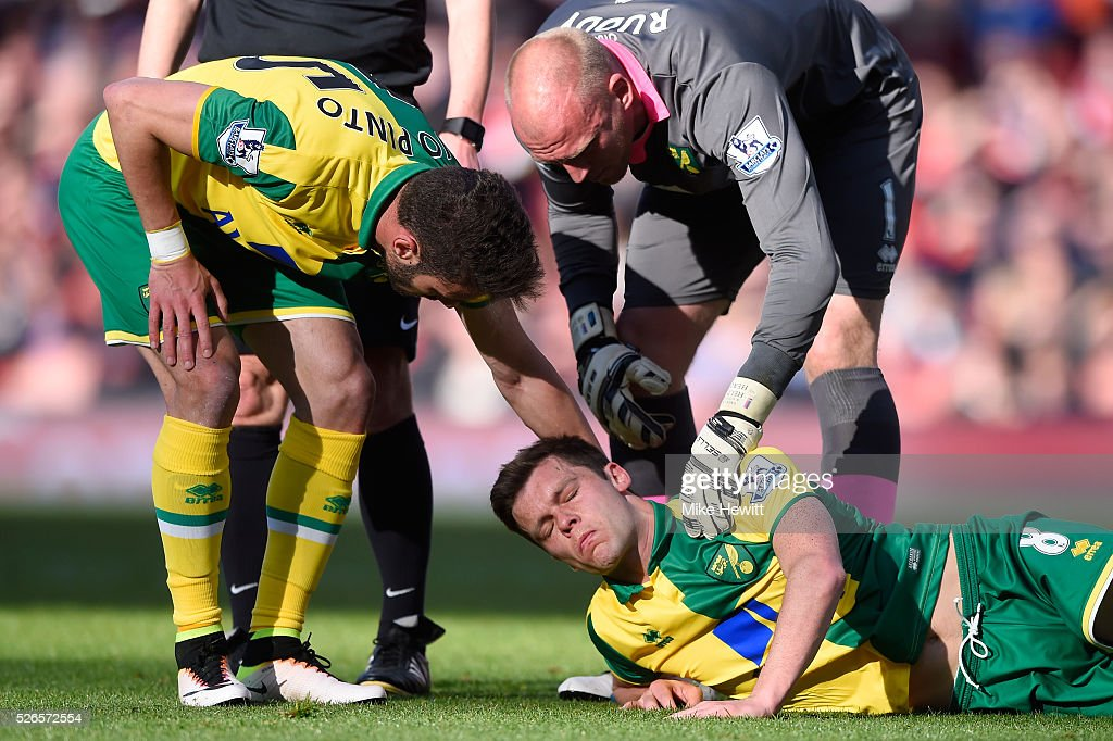 Jonathan Howson of Norwich City lies injured while Ivo Pinto and John Ruddy talk to him during the Barclays Premier League match between Arsenal and Norwich City at The Emirates Stadium on April 30, 2016 in London, England