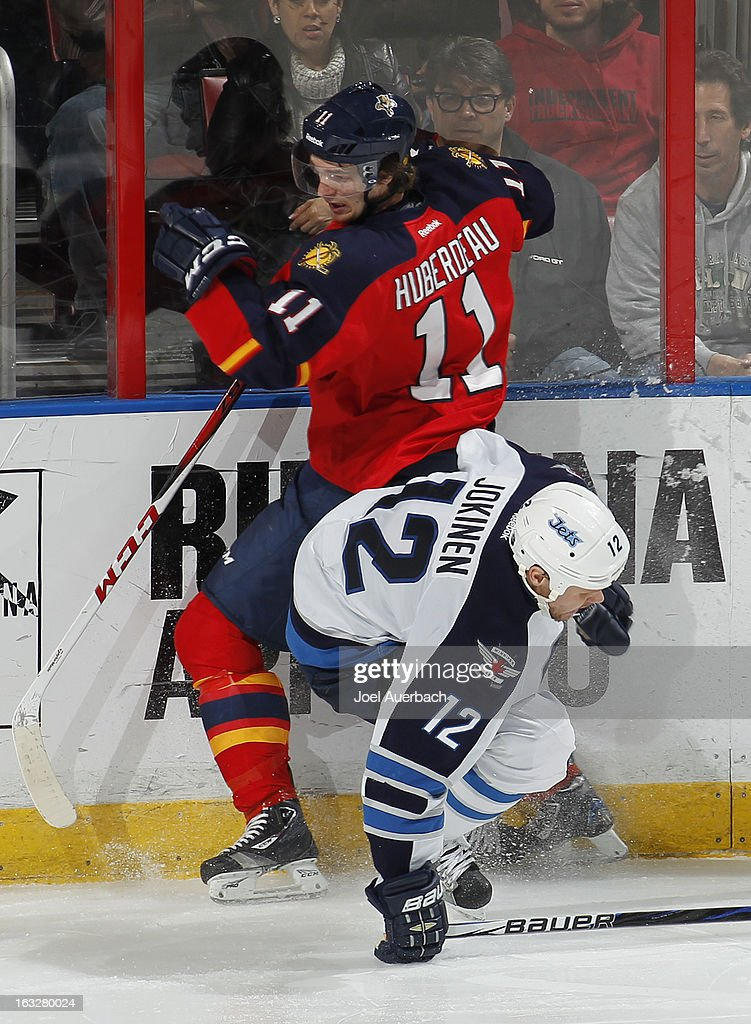 Jonathan Huberdeau #11 of the Florida Panthers and Olli Jokinen #12 of the Winnipeg Jets collide along the boards at the BB&T Center on March 5, 2013 in Sunrise, Florida. The Panthers defeated the Jets 4-1.