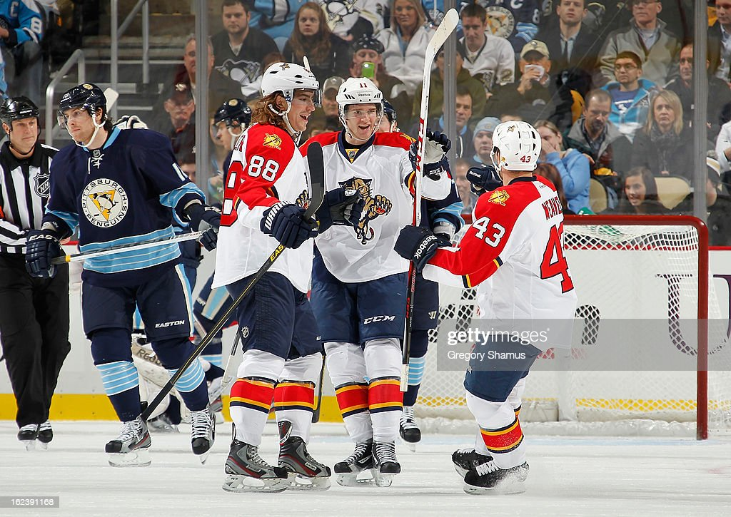 Jonathan Huberdeau #11 of the Florida Panthers celebrates his goal with Peter Mueller #88 and Mike Weaver #43 during the game against the Pittsburgh Penguins on February 22, 2013 at Consol Energy Center in Pittsburgh, Pennsylvania.