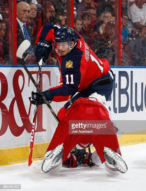 Jonathan Huberdeau of the Florida Panthers chases a puck into the corner past a Columbus Blue Jackets player who fell to the ice at the BBT Center on...