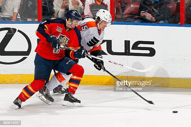 Jonathan Huberdeau of the Florida Panthers crosses sticks with Tye McGinn of the Philadelphia Flyers at the BBT Center on April 8 2014 in Sunrise...