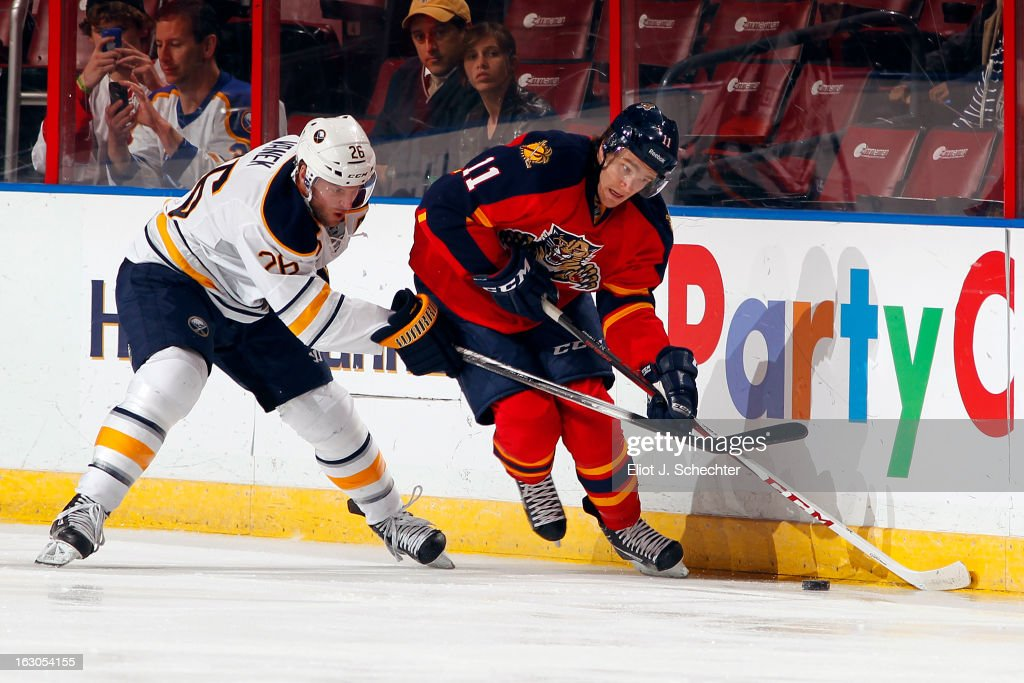 Jonathan Huberdeau #11 of the Florida Panthers digs the puck out from the boards against Thomas Vanek #26 of the Buffalo Sabres at the BB&T Center on February 28, 2013 in Sunrise, Florida.