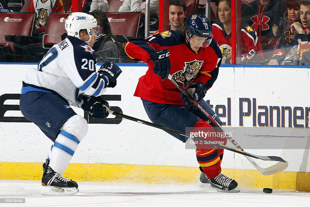 Jonathan Huberdeau #11 of the Florida Panthers digs the puck out from the boards against Antti Miettinen #20 Winnipeg Jets at the BB&T Center on March 8, 2013 in Sunrise, Florida.