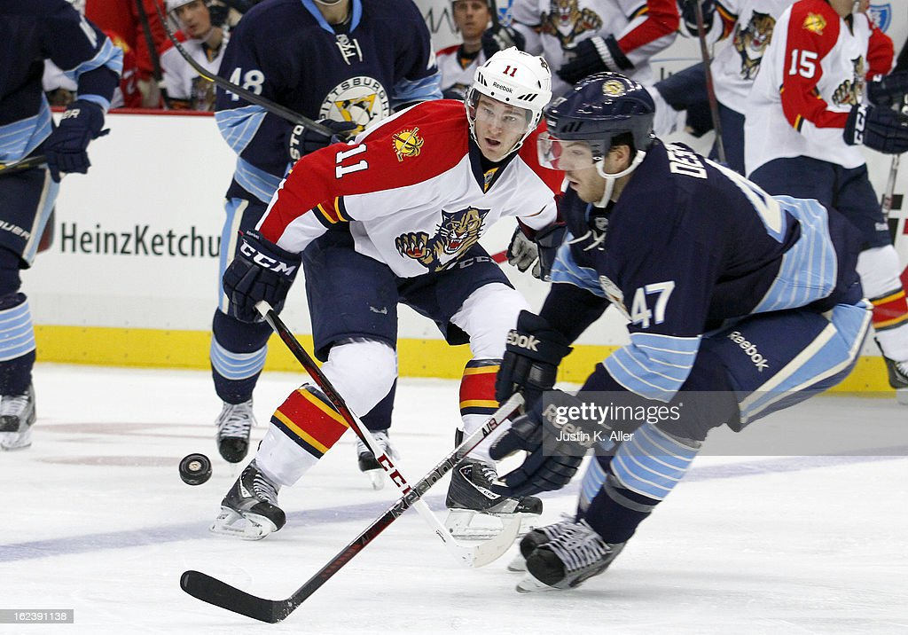 Jonathan Huberdeau #11 of the Florida Panthers handles the puck in front of Simon Despres #47 of the Pittsburgh Penguins during the game at Consol Energy Center on February 22, 2013 in Pittsburgh, Pennsylvania.