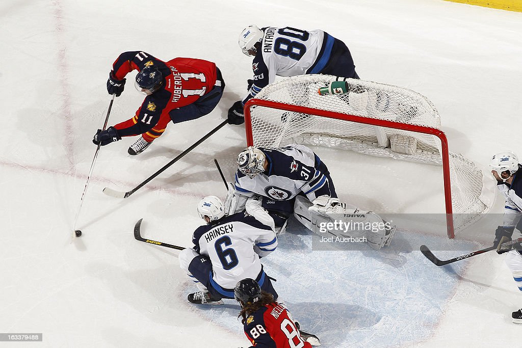 <a gi-track='captionPersonalityLinkClicked' href=/galleries/search?phrase=Jonathan+Huberdeau&family=editorial&specificpeople=7144196 ng-click='$event.stopPropagation()'>Jonathan Huberdeau</a> #11 of the Florida Panthers is unable to wrap the puck around the post to score a goal as Goaltender Ondrej Pavelec #31 of the Winnipeg Jets defends the net at the BB&T Center on March 8, 2013 in Sunrise, Florida.