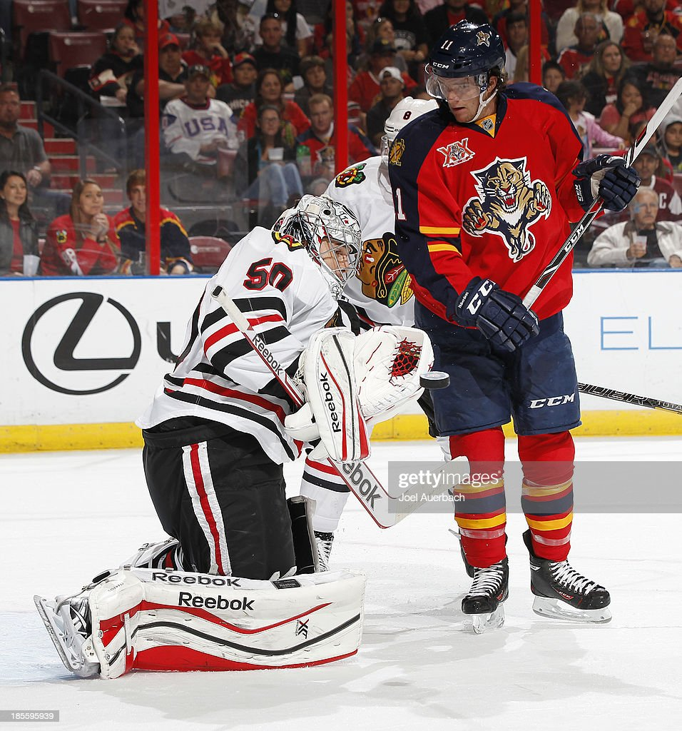 Jonathan Huberdeau #11 of the Florida Panthers looks on as goaltender Corey Crawford #50 of the Chicago Blackhawks makes a glove save at the BB&T Center on October 22, 2013 in Sunrise, Florida.