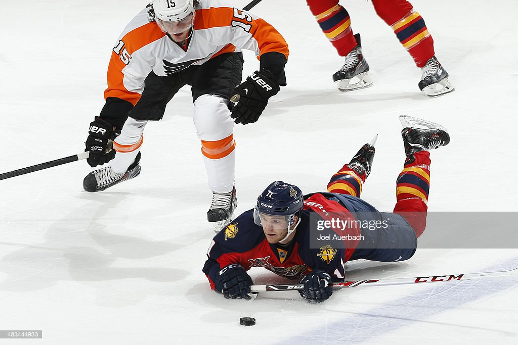 Jonathan Huberdeau #11 of the Florida Panthers loses control of the puck after being checked by Tye McGinn #15 of the Philadelphia Flyers at the BB&T Center on April 8, 2014 in Sunrise, Florida. The Flyers defeated the Panthers 5-2.