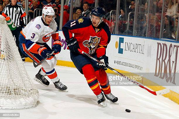 Jonathan Huberdeau of the Florida Panthers skates with the puck against Travis Hamonic of the New York Islanders at the BBT Center on March 7 2015 in...