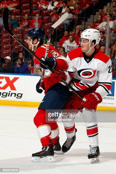 Jonathan Huberdeau of the Florida Panthers tangles with Brett Pesce of the Carolina Hurricanes at the BBT Center on March 21 2017 in Sunrise Florida