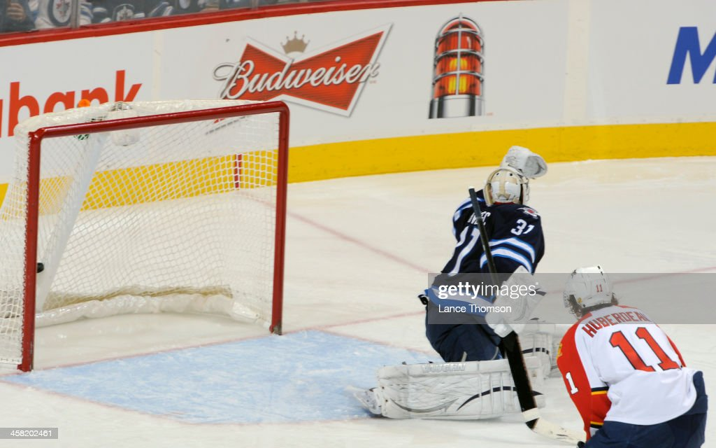 <a gi-track='captionPersonalityLinkClicked' href=/galleries/search?phrase=Jonathan+Huberdeau&family=editorial&specificpeople=7144196 ng-click='$event.stopPropagation()'>Jonathan Huberdeau</a> #11 of the Florida Panthers watches as the puck flies into the net behind goaltender Ondrej Pavelec #31 of the Winnipeg Jets for a second period goal at the MTS Centre on December 20, 2013 in Winnipeg, Manitoba, Canada.