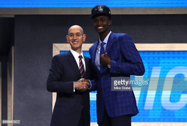 Jonathan Isaac walks on stage with NBA commissioner Adam Silver after being drafted sixth overall by the Orlando Magic during the first round of the...