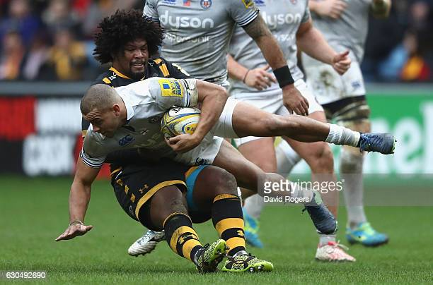 Jonathan Joseph of Bath is tackled by Ashley Johnson during the Aviva Premiership match between Wasps and Bath Rugby at The Ricoh Arena on December...