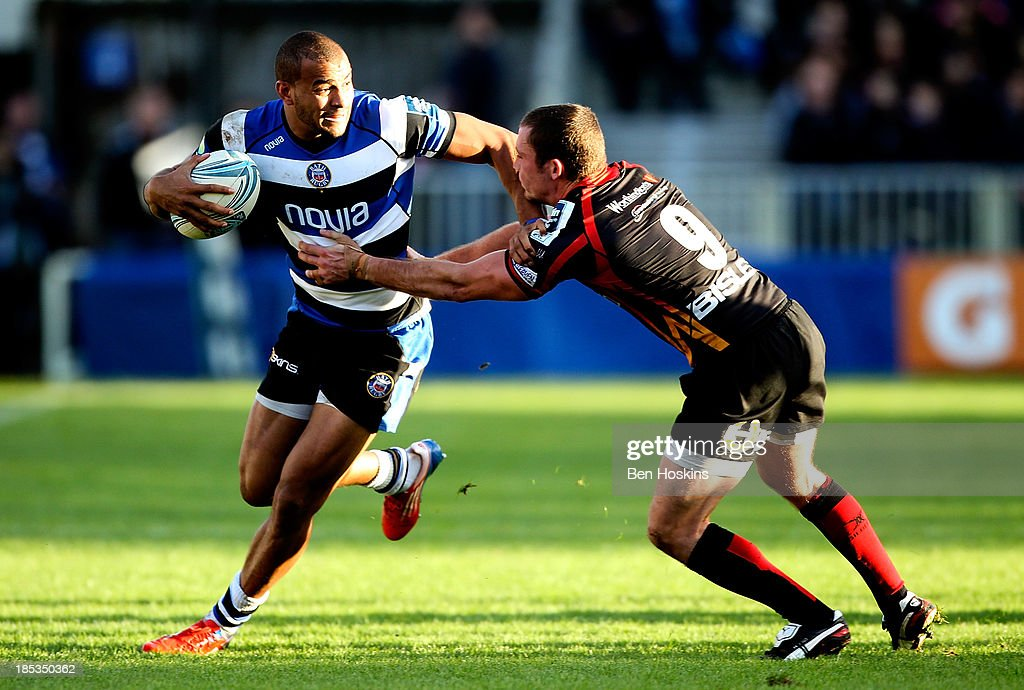 Jonathan Joseph of Bath is tackled by Richie Rees (R) of Newport during the Amlin Challenge Cup match between Bath and Newport Gwent Dragons at Recreation Ground on October 19, 2013 in Bath, England.
