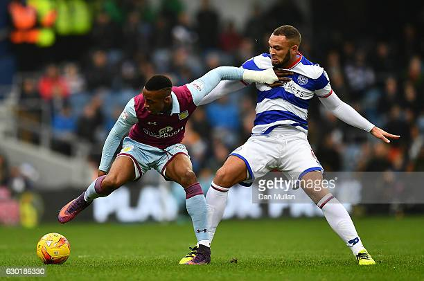 Jonathan Kodjia of Aston Villa holds off Joel Lynch of Queens Park Rangers during the Sky Bet Championship match between Queens Park Rangers and...