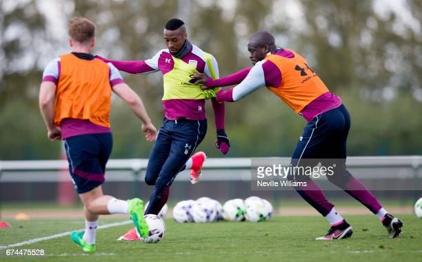 Jonathan Kodjia of Aston Villa in action with team mate Chris Samba during a training session at the club's training ground at Bodymoor Heath on...