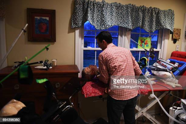 Jonathan Lasko carefully lifts up his son Max age 35 who suffers from spinal muscular atrophy from his activity bench in the kitchen area at their...