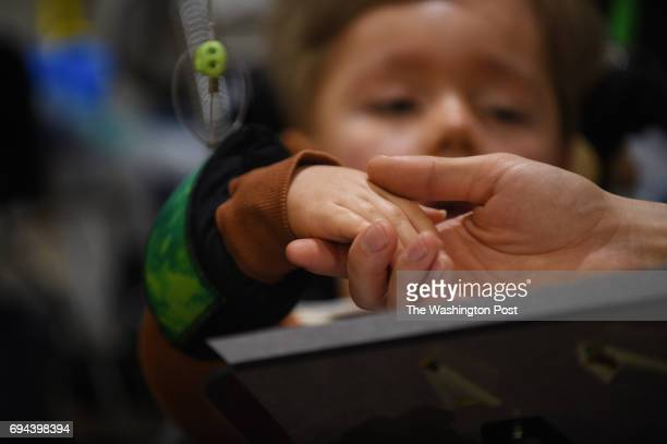 Jonathan Lasko holds the hand of his son Max age 35 who suffers from spinal muscular atrophy at their family home in Derwood MD March 3 2017 Spinal...