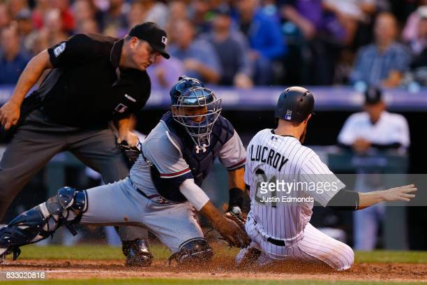 Jonathan Lucroy of the Colorado Rockies slides safely under the tag of catcher Kurt Suzuki of the Atlanta Braves as home plate umpire Dan Bellino...