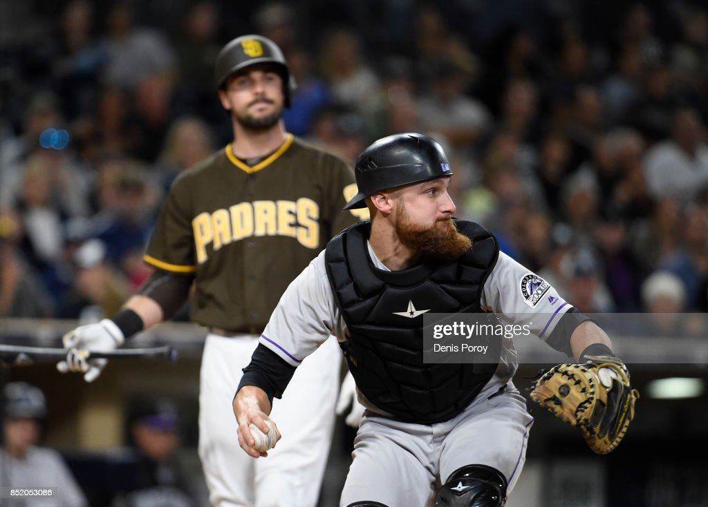 Jonathan Lucroy #21 of the Colorado Rockies throws to second base as Austin Hedges #18 of the San Diego Padres looks on during the fifth inning of a baseball game at PETCO Park on September 22, 2017 in San Diego, California. Hedges struck out and Erick Aybar #8 of the San Diego Padres was out at second base.