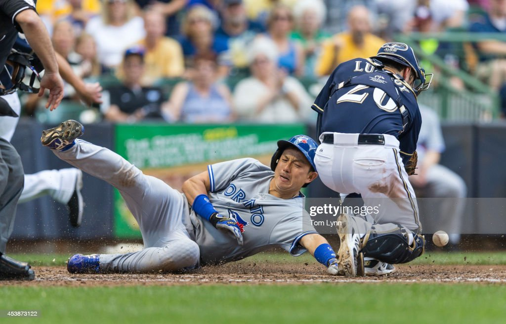 <a gi-track='captionPersonalityLinkClicked' href=/galleries/search?phrase=Jonathan+Lucroy&family=editorial&specificpeople=5732413 ng-click='$event.stopPropagation()'>Jonathan Lucroy</a> #20 of the Milwaukee Brewers can not make the catch to put the tag on <a gi-track='captionPersonalityLinkClicked' href=/galleries/search?phrase=Munenori+Kawasaki&family=editorial&specificpeople=690355 ng-click='$event.stopPropagation()'>Munenori Kawasaki</a> #66 of the Toronto Blue Jays at Miller Park on August 20, 2014 in Milwaukee, Wisconsin.