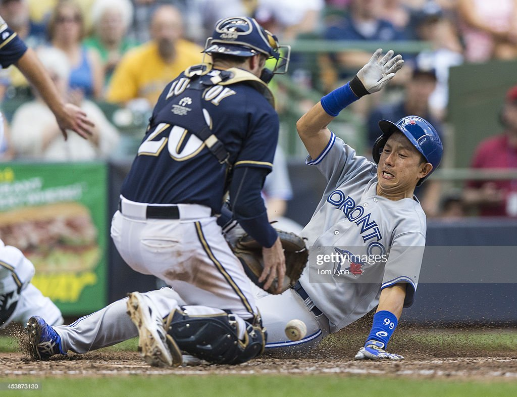 Jonathan Lucroy #20 of the Milwaukee Brewers can not make the catch to put the tag on Munenori Kawasaki #66 of the Toronto Blue Jays at Miller Park on August 20, 2014 in Milwaukee, Wisconsin.