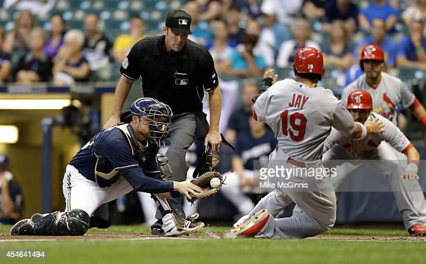 Jonathan Lucroy of the Milwaukee Brewers is late with the tag as Jon Jay of the St Louis Cardinals slides into home plate in the top of the first...