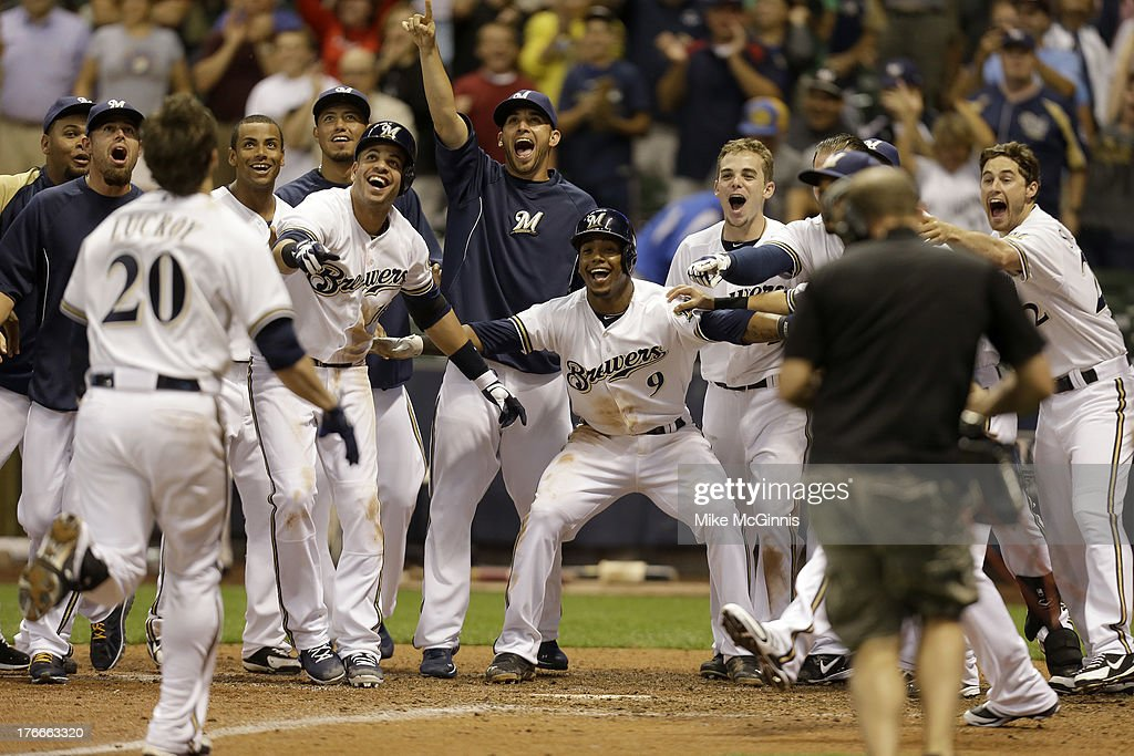 Jonathan Lucroy #20 of the Milwaukee Brewers is welcomed by teammates at home plate after hitting a two-run, walk-off home run in the bottom of the ninth inning against the Cincinnati Reds at Miller Park on August 16, 2013 in Milwaukee, Wisconsin.