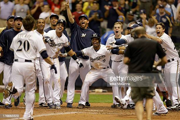 Jonathan Lucroy of the Milwaukee Brewers is welcomed by teammates at home plate after hitting a tworun walkoff home run in the bottom of the ninth...