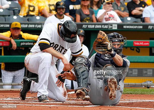 Jonathan Lucroy of the Milwaukee Brewers tags out Neil Walker of the Pittsburgh Pirates in the second inning during the game at PNC Park June 8 2014...