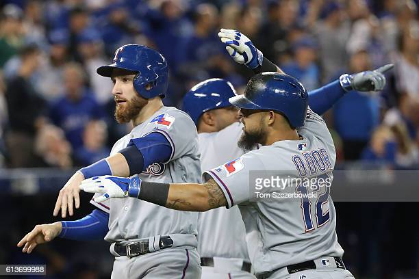 Jonathan Lucroy of the Texas Rangers celebrates with teammate Rougned Odor after scoring on a two run double hit by Mitch Moreland in the sixth...
