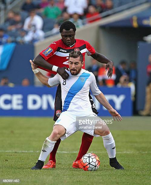 Jonathan Marquez of Guatemala tries to hold off Aubrey David of Trindad and Tobago during a match in the 2015 CONCACAF Gold Cup at Soldier Field on...