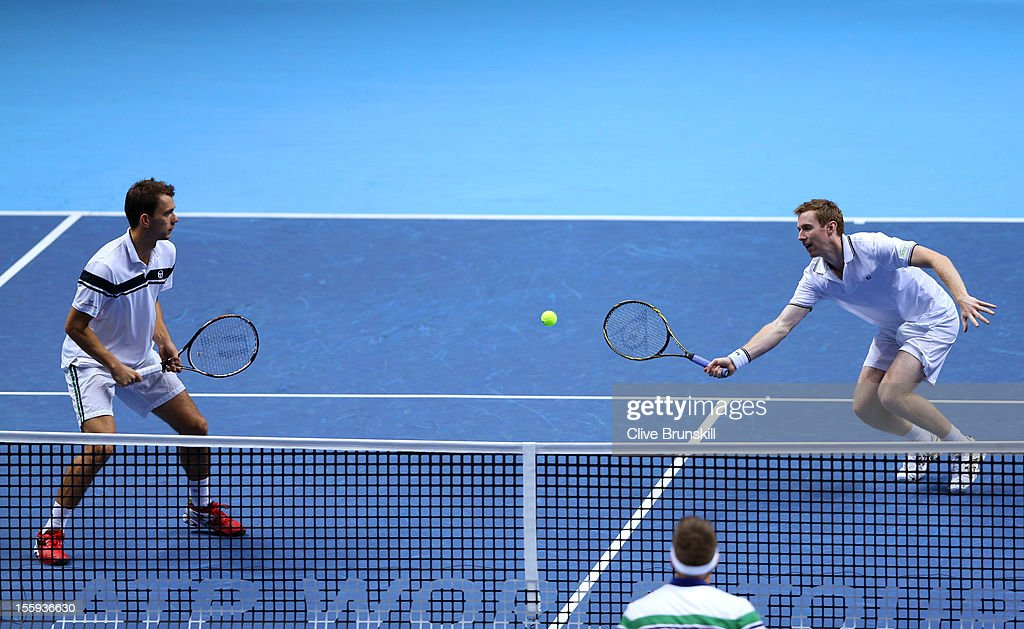 Jonathan Marray of Great Britain returns a shot next to Frederik Nielsen of Denmark reacts during their men's doubles match against Robert Lindstedt...